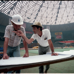 Workers looking at plans for repair work in the Astrodome